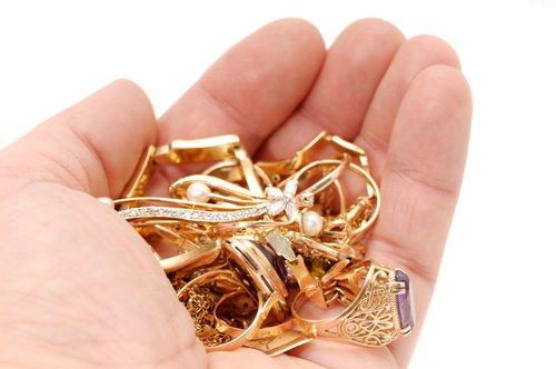Mano que sostiene joyas de oro