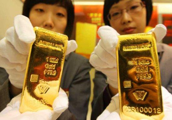 Dos mujeres chinas con lingotes de oro en las manos