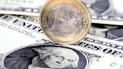 Moneda euro sobre billetes de dólar