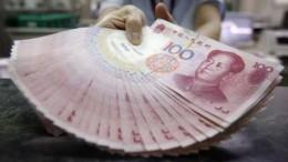 Billetes de 100 yuanes chinos cojidos de una mano