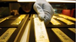 Mano con guante cogiendo lingote de oro
