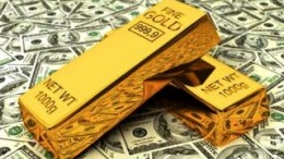 Lingotes de oro encima de billetes de dólares
