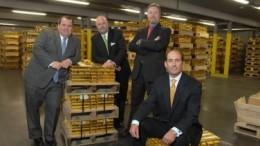Varias personas sentadas sobre palets de lingotes de oro