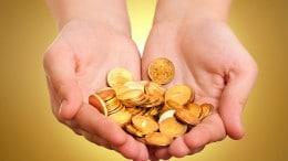 Monedas de oro en dos manos