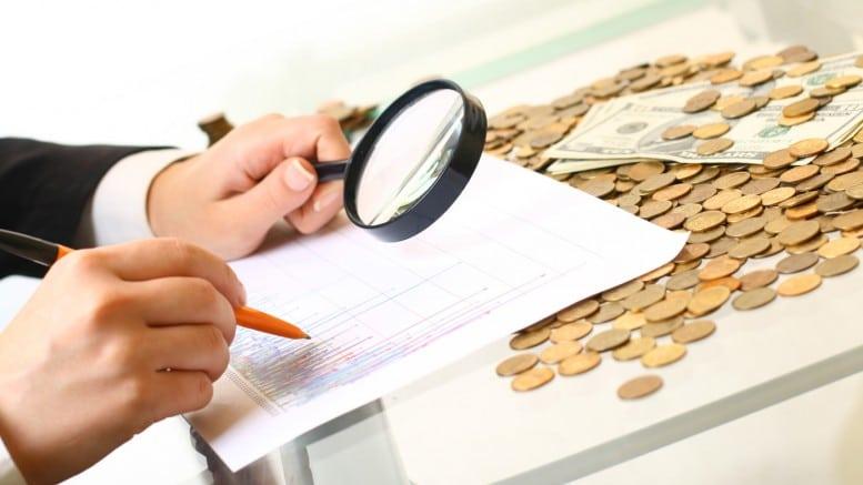 Mano, papel y monedas con un analisis